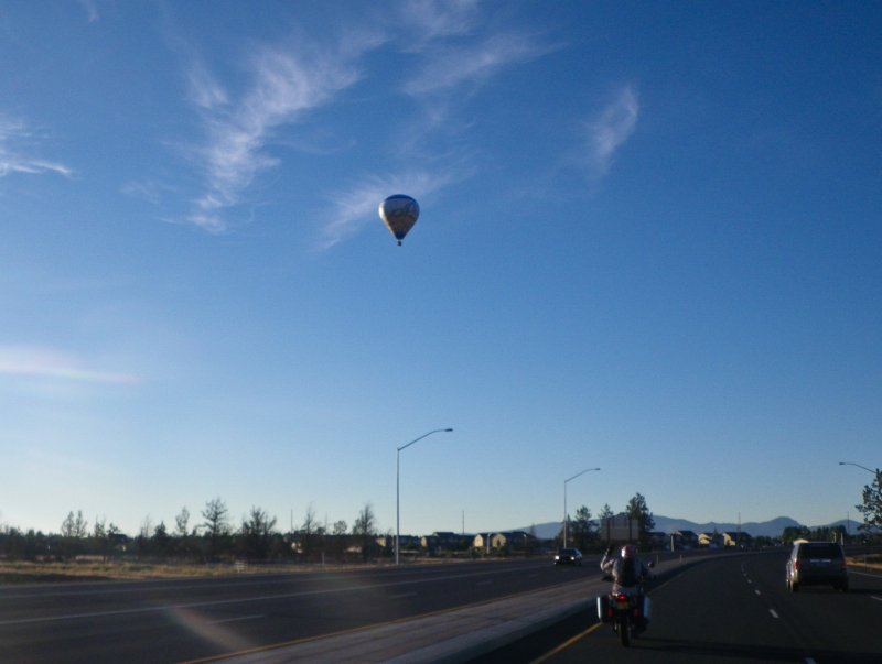 Hot air balloon on the road out of town in the morning.