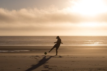Nephew Jake playing soccer on the beach at sunset.